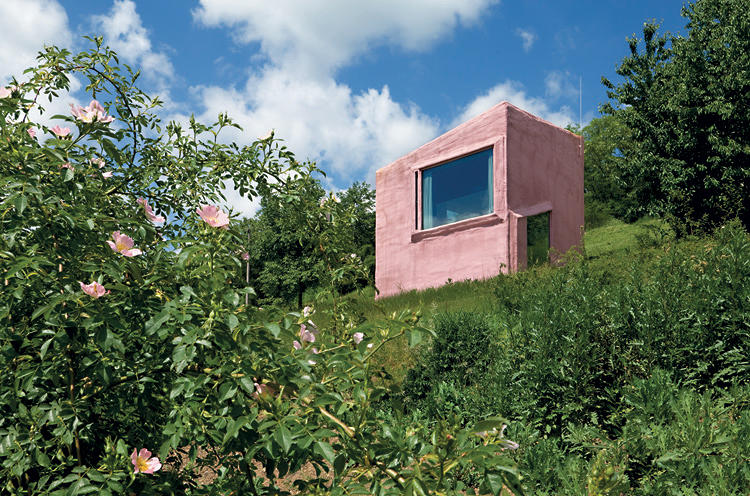 <p>This box on a hill has two attention-grabbing features: its Pepto-colored exterior and its interior slant. The color refers to the designers' favorite building, Ludwig Leo's Versuchsanstalt fur Wasserbau und Schiffbau, in Berlin, whose external pipework is painted pastel pink. The steep incline is in part a response to the client's request for a movie theater with raked seating. The lower level is connected to the upper by bright-green ramps, which provide more floor space than traditional stairs. The floors are covered in an anti-skid material common in sports facilities.</p>