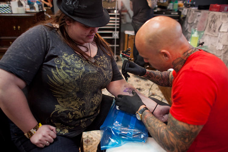 <p>NY Ink tattoo artist Ami James works on a fan.</p>