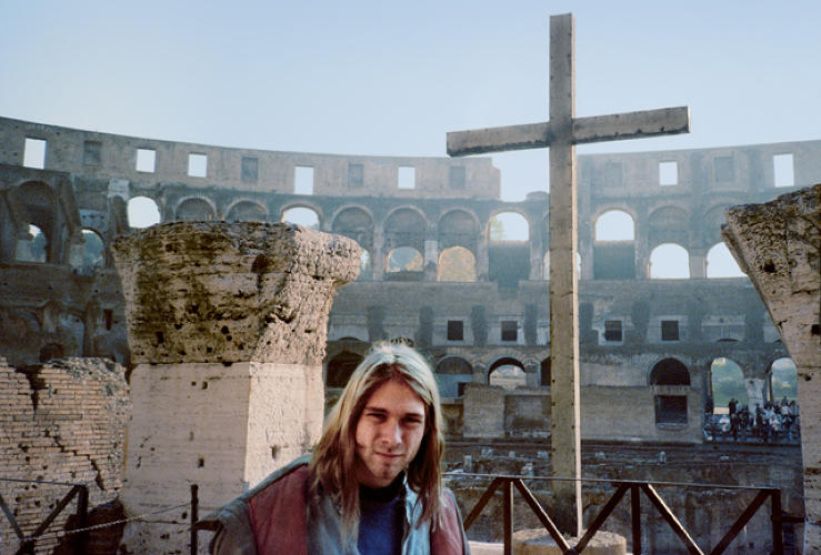 <p>Kurt Cobain, age 22 here, poses for a snapshot at the Coliseum in Rome during a day off from tour. Source: <a href=&quot;https://itunes.apple.com/us/book/experiencing-nirvana-grunge/id575827071?mt=11&quot; target=&quot;_blank&quot;><em>Experiencing Nirvana: Grunge In Europe, 1989</em></a></p>
