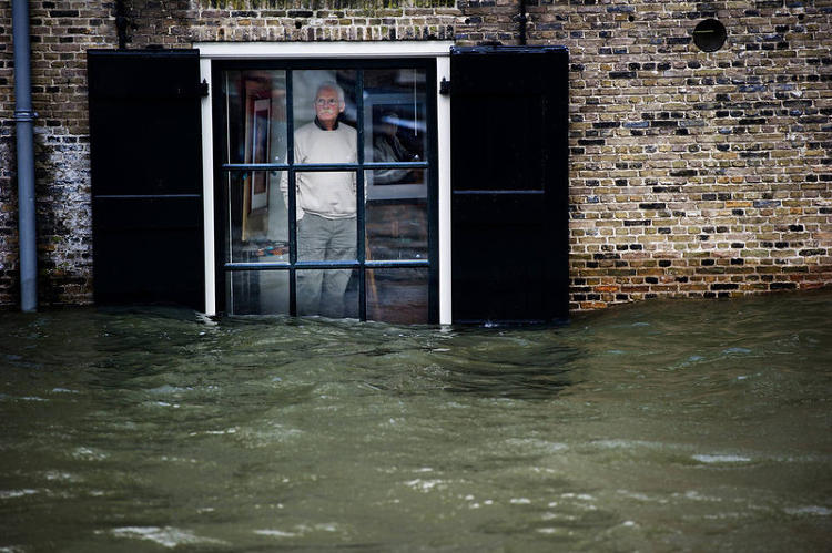 <p>A Dutch resident seems to still be processing the high waters level he sees through his window, in Dordrecht on January 5, 2012.</p>