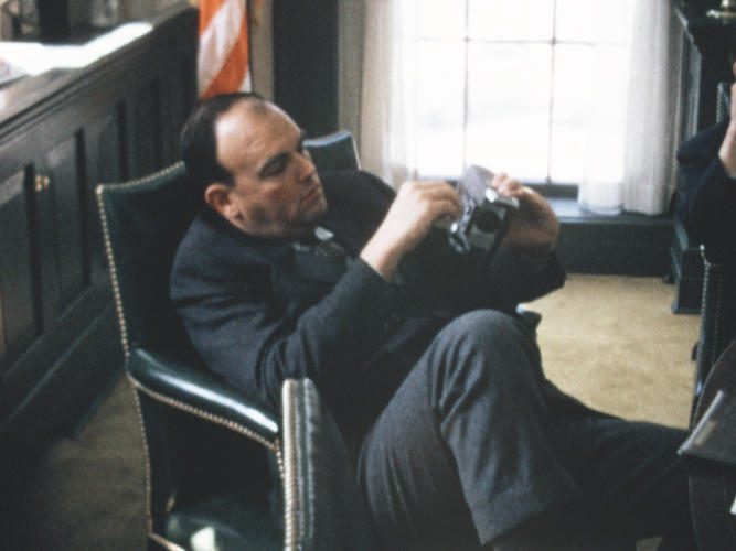 <p>Chief Domestic Advisor John Ehrlichman fiddles with his Super 8 camera during a particularly boring staff meeting at the White House.</p>