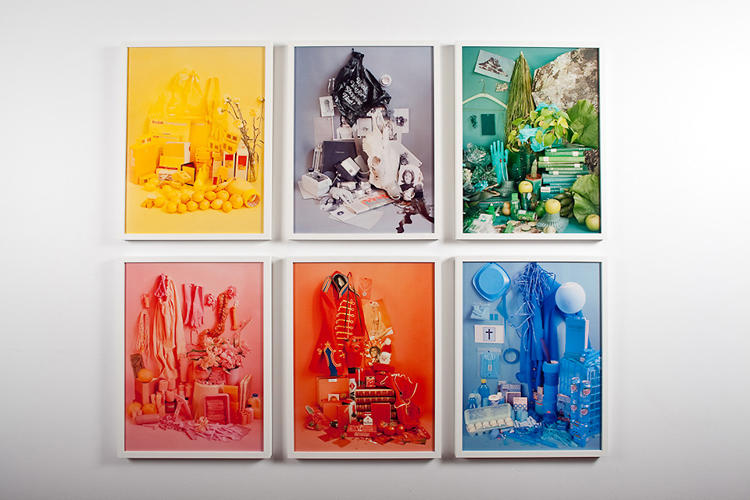 <p>Her color-coded still lifes hang alongside the installation.</p>