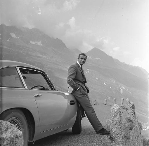 <p>Sean Connery leans against an Aston Martin DB5 in <em>Goldfinger</em>.</p>