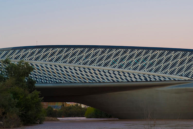 <p>&quot;Four intersecting but distinct pods make up this curving pavilion and footbridge, which also acted as the entrance to the Zaragoza International Expo. 29,000 fibre-reinforced concrete panels in different shades create a complex 'shark-skin' pattern.&quot;</p>