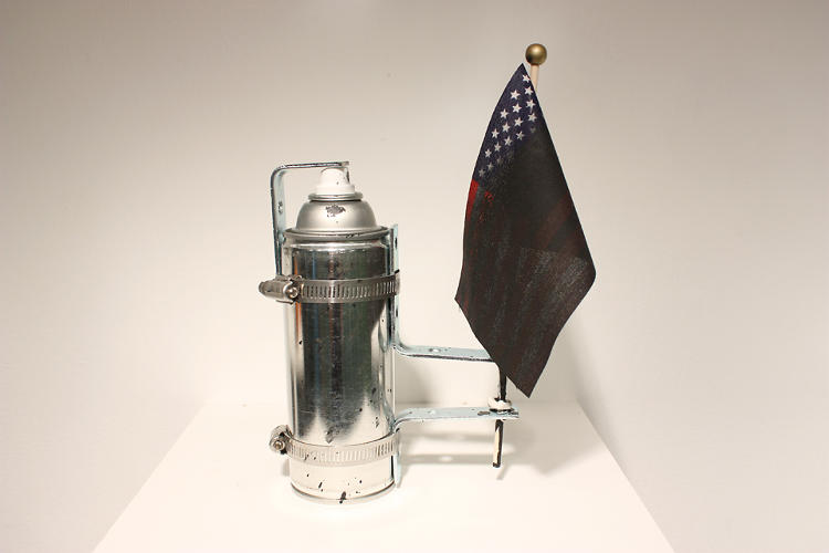 <p>In this provocative piece, a black spray can rapidly defaces a miniature American flag.</p>