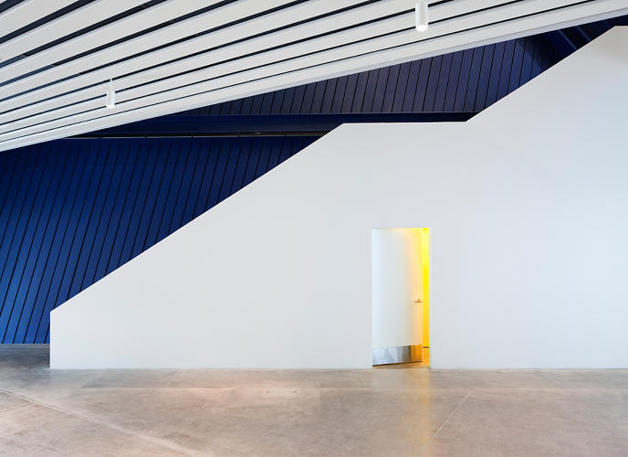 <p>Inside, the walls are painted a deep cobalt, contrasting with the white interior partitions.</p>