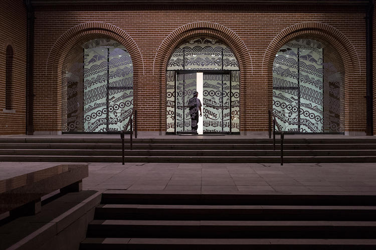 <p>A new installation at Rice Gallery uses corporate logos and slogans to create a mandala-esque pattern on the gallery floor and walls.</p>