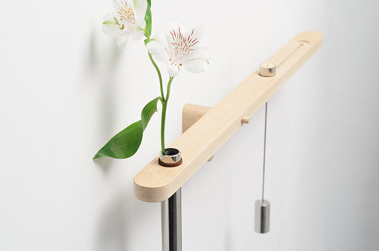 <p>The thin capsule-like vase is filled with water. When the liquid starts to evaporate, the balance is thrown off, and the assemblage tilts downward. Translation: it's time to water your plants.</p>