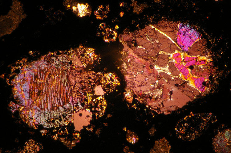 <p>A micrograph of a pair of chondrules (round granules embedded in astral stones) from the Allende meteorite. The colors represent the natural frequencies of the minerals that make up the crystals, which tells you what type of mineral you're looking at. In this photo, the chondrule at left is barred olivine; the one on the right is porphyritic pyroxene and slightly shocked due to an impact.</p>
