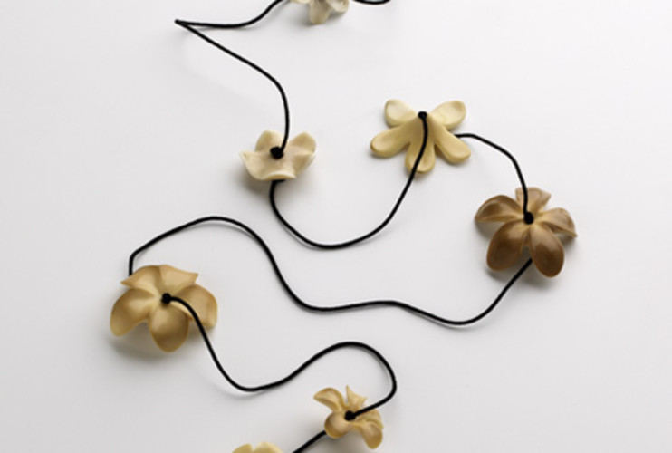 <p> Muehling created a lei by stringing flowers made from vegetable ivory on a black silk cord.  </p>
