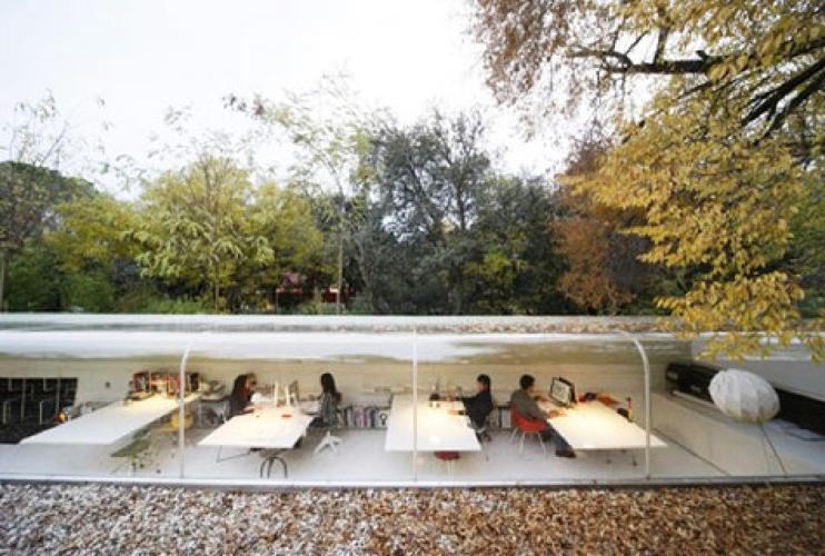 <p>The Spanish architects Jose Selgas and Lucia Cano have created a studio for their firm, Selgascano, nestled in the woods near Madrid. The office is encased in a long pod-like tube that is half-submerged in the ground to diminish its profile on the land. The north facing wall of the tube is enclosed in curving transparent acrylic, which allows staffers some exposure to the seasons and a dappled light filtering through the overhanging trees. </p> <p><a href=&quot;http://www.fastcompany.com/blog/michael-cannell/cannell/would-you-work-under-tree&quot;>Read More</a></p>