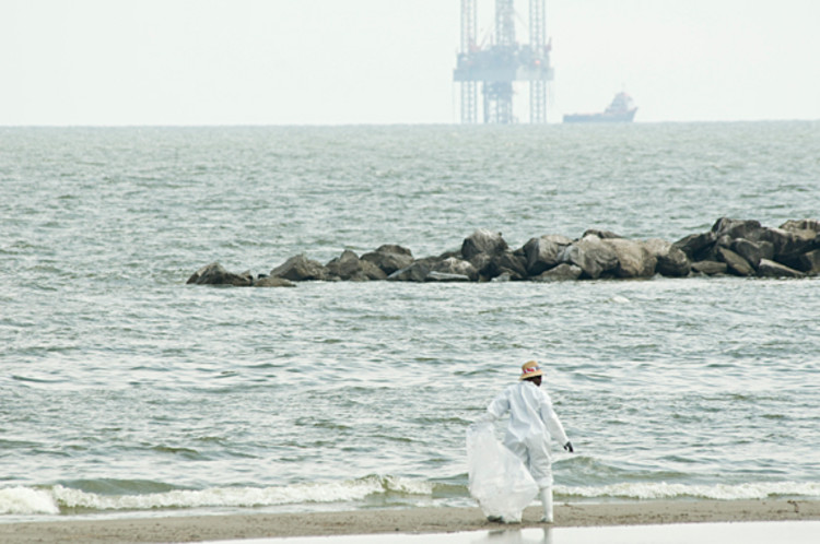 An official BP clean-up worker searches the shoreline for signs of more tar balls at Grand Isle, La.