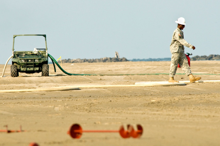 A soldier hauls gas to refuel vehicles being used in the clean up effort.