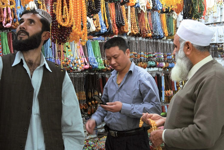 Afghan customers at Yiwu's Trade Mart negotiate with a Chinese shopkeeper over the price of beads.