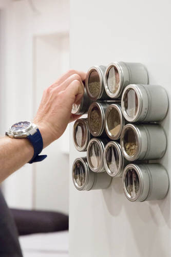 <p>Spice containers are cleverly stored in magnetic containers placed on metal cabinetry.</p>