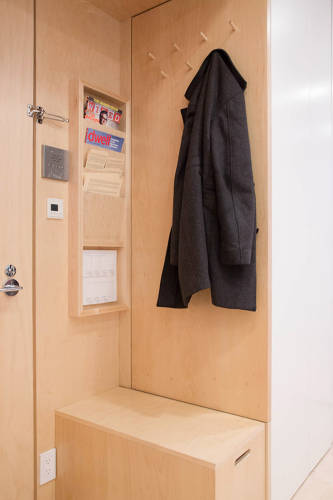 <p>At the entrance of Graham's apartment is a storage sitting area, with hooks for jackets and magazine and mail shelving.</p>