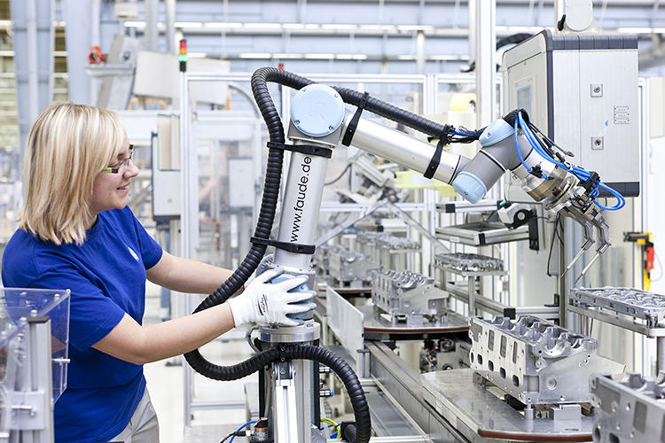 <p>At one of the world's largest automotive engine factories, robots are starting to come out of their cages to work with people.</p>