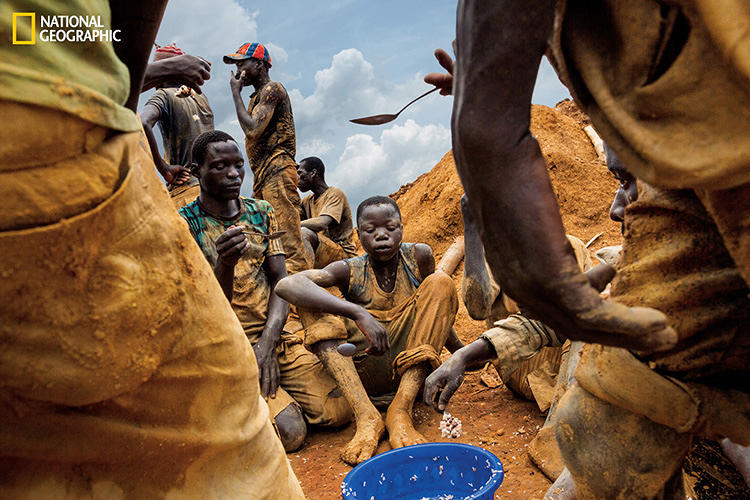 <p>A boy waits his turn for spoonfuls of rice and beans in Pluto. In some areas of eastern Congo up to 40% of gold miners are children, often forcibly recruited by militias.</p>