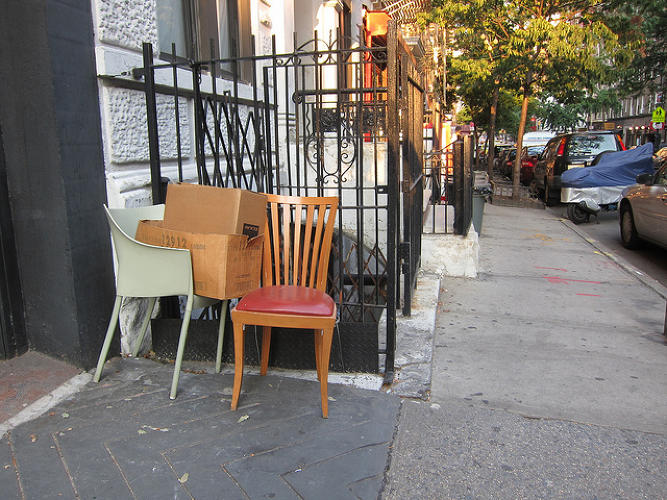"<p><em>""Here, You Take These"" Chairs</em>: It appears as if the plastic chair is tired of bearing its burden and wants to pass some off on the wooden chair. Taken in New York City in August 2012.</p>"