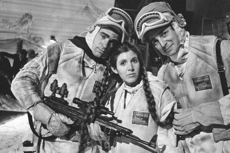 <p>Some extras snuggle up to Carrie Fisher for warmth. Who can blame them?</p>