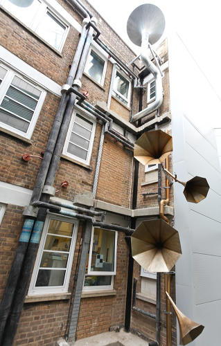 <p>Since the tall space was narrow and strangely shaped, the designers realized they couldn't really cover up the older building; it would block too much light. Instead of hiding anything, they decided to celebrate the building's existing quirks.</p>