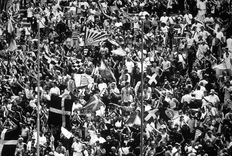 <p>Silver gelatin print 16 x 20 in.<br /> This still photograph of Italian soccer fans is part of a series that captures the sport as a mass spectacle.<br /> Lyle Ashton Harris</p>