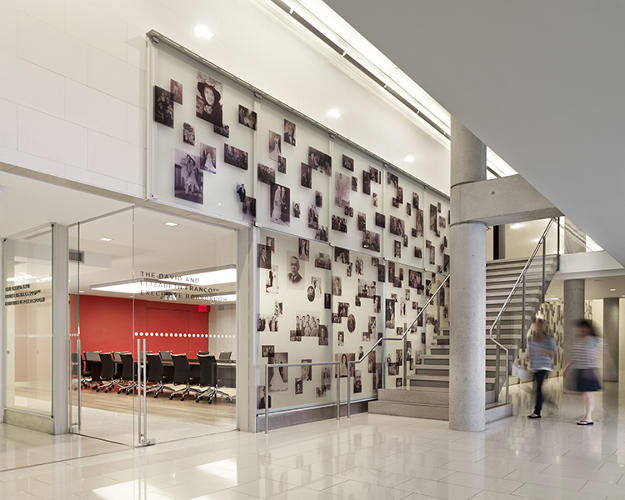 <p>A key innovation is the glass wall along the wide central stair that dramatically incorporates more than 400 images of family members who immigrated to the U.S. The building design funnels natural light into the stairwell, despite it being in the center, while elevators are featured less prominently nearby.</p>