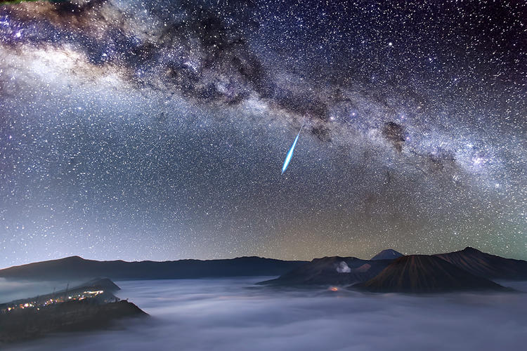 <p>A bright meteor streaks across the magnificent night sky over the smoke-spewing Mount Bromo just one day before the peak of the Eta Aquarid meteor shower, which is caused by Halley's Comet. Mount Bromo is one of the most well-known active volcanoes in East Java, Indonesia.</p>