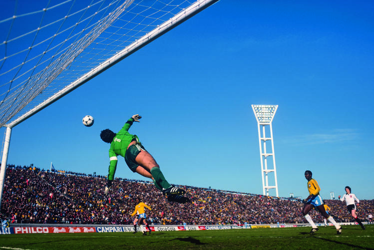 <p>Brazilian goalkeeper Emerson Leão leaps toward the ball in a game against Austria.</p>