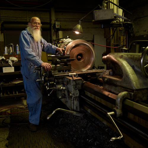 <p>Superior Lidgerwood Mundy, Superior, established 1895 as Superior Iron Works by Frank Hayes. SLM makes hoists and cables for the marine industry. Machine lathe operator Brent is pictured on his last full day of work before retirement.</p>