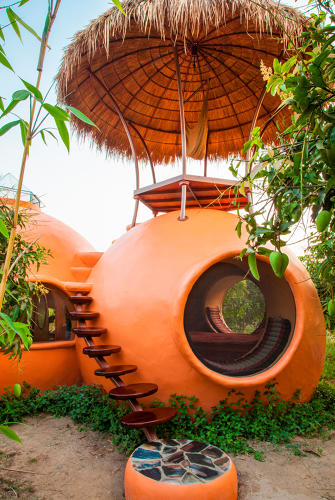 <p>This Dr. Seussian orange refuge sits amidst a large organic mango farm. Completed by a small community of builders in just six weeks for under $6,000, the dome-shaped hut includes a handmade staircase that winds up to a rooftop patio shaded by a shaggy palapa.</p>