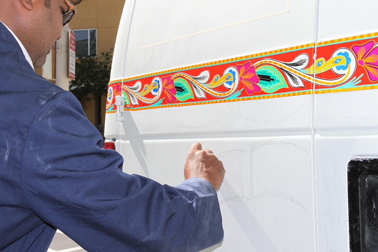 <p>Haider Ali begins to fill in the white spaces of his 2014 Jingle Truck design.</p>