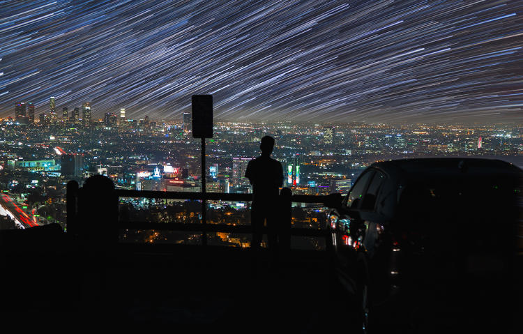 <p>Silhouetted Man watches star trails over the lights of Los Angeles 2014.</p>