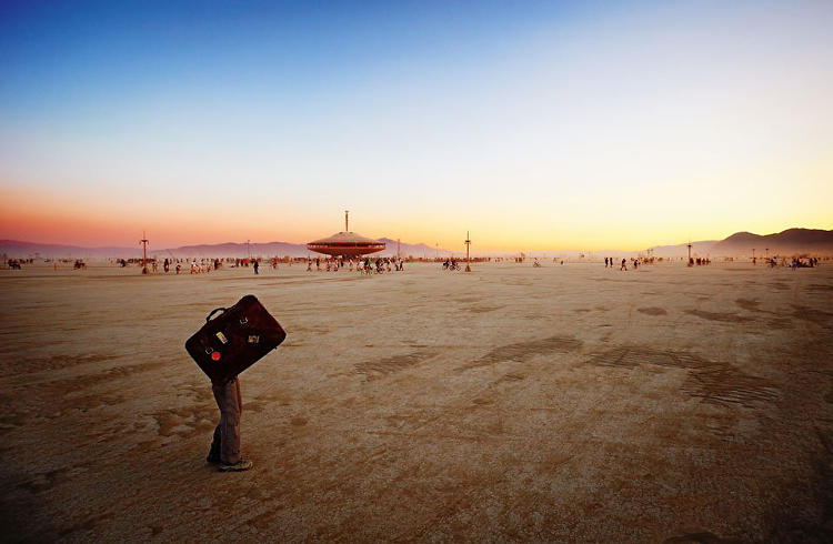 <p>A piece of lonely lost luggage – performer Pi Feathersword – wanders disconsolately across the playa.</p>