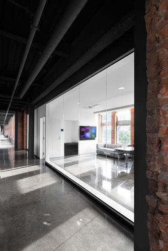 <p>The floors are polished concrete. Glass-walled offices are built into the perimeter of the office.</p>