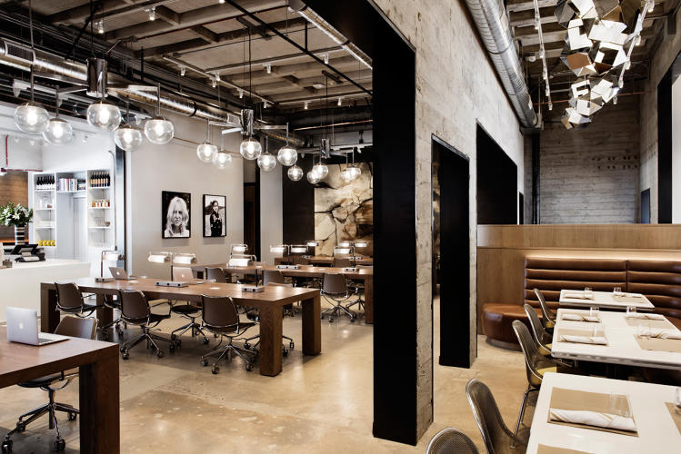 <p>A workspace adjacent to the coffee shop provides an area for working, meetings, or enjoying a snack. A custom geometric chandelier by Gabriel Scott hangs above custom leather banquettes.</p>