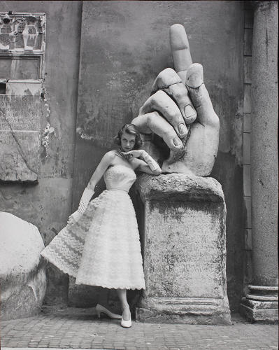 <p>Sorelle Fontana model alongside the hand of the colossal statue of Constantine in the courtyard of the Musei Capitolini in Rome, 1952.  This image was part of a feature published in<br /> La Donna, June 1952.</p>