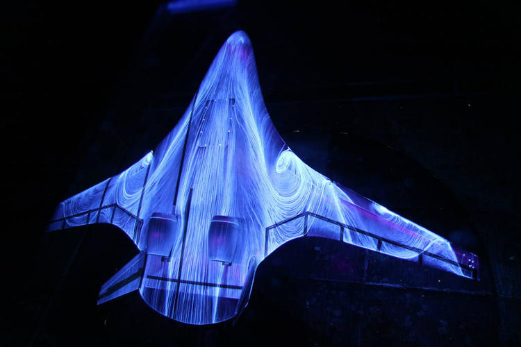 <p>This hybrid wing plane concept is being tested in a wind tunnel using a 5% scale model. The patterns reveal drag on the plane's body, thanks to a fluorescent oil sprayed on the model. Image: NASA Langley/Preston Martin.</p>