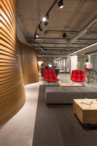 <p>Upon entering the 72,000-square-foot office, you're greeted with an undulating wood wall that mimics biking terrain.</p>