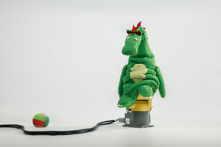 <p>One robot is covered in a soft dragon costume, turning it into a toy.</p>