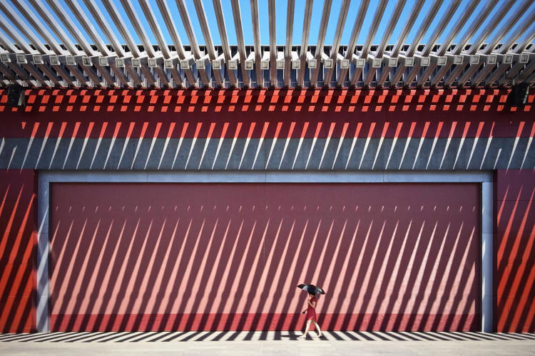 <p>In front of this Chinese red wall walks a lady in a red dress.</p>