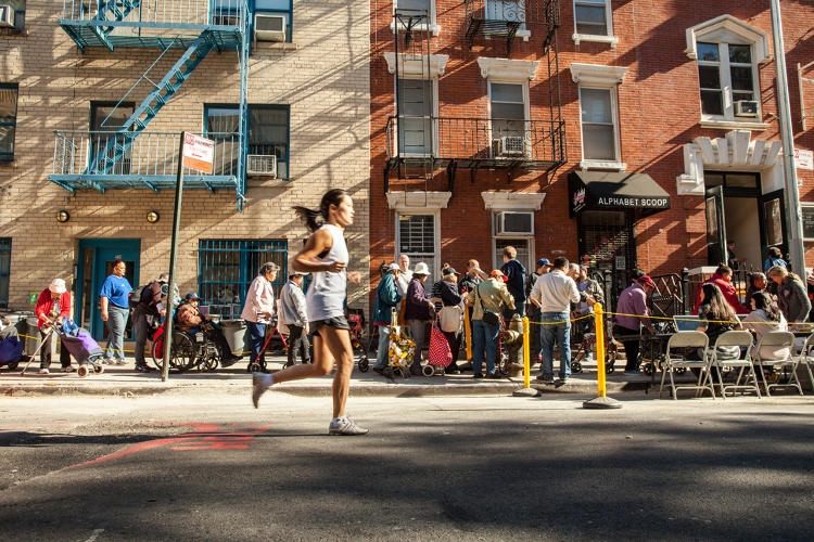 <p>Saturday morning on the Lower East Side/East Village, a runner cruises past the food line at Father's Heart Pantry.</p>