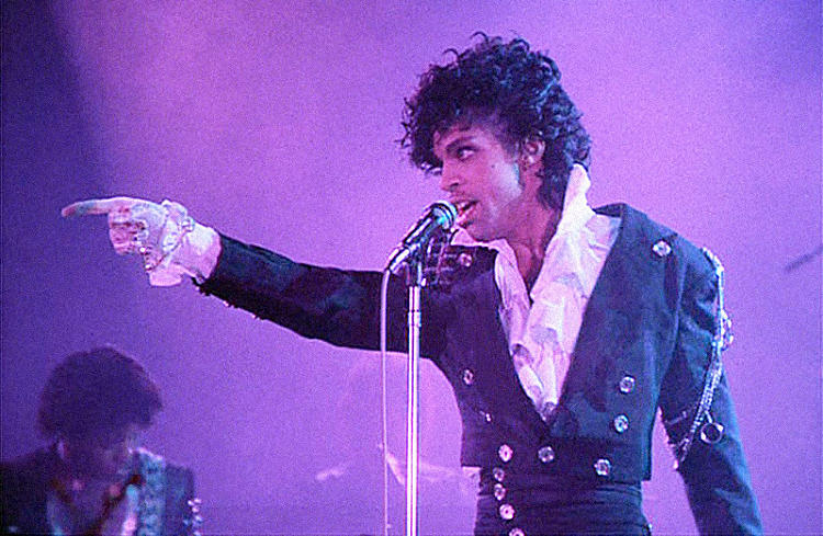 <p>Prince performing in 1984 in his signature look from his <em>Purple Rain</em>-era: a ruffle shirt, purple suit, eyeliner and a Jheri curl.</p>