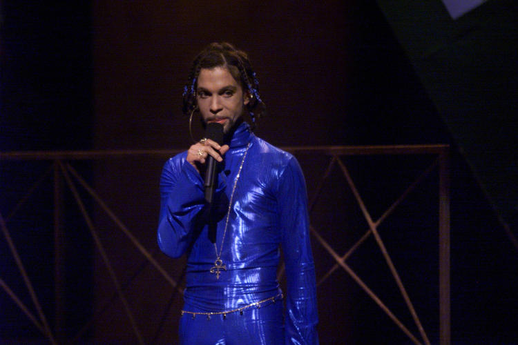 <p>Prince in a metallic blue jumpsuit, blue beaded braids and an enormous hoop earring at the MTV VMAs in 1999.</p>