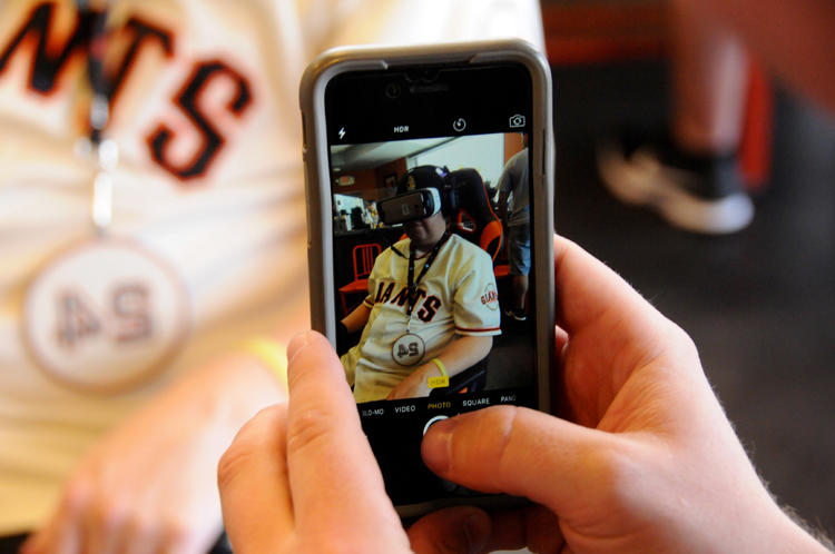 <p>A Giants employee shoots a picture of a fan watching VR.</p>