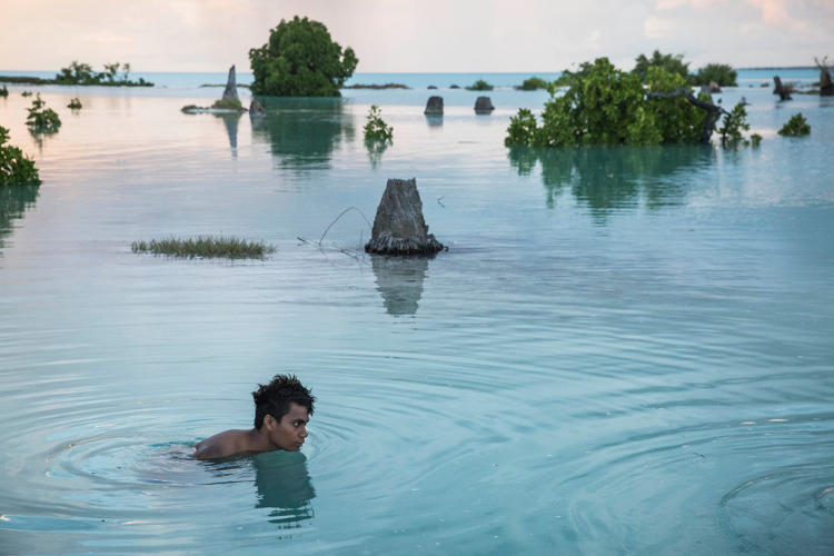 <p>Peia Kararaua, 16, swims in the flooded area of Aberao village that is located in Tarawa atoll, Kiribati. Kiribati is one of the countries most affected by sea level rise. During high tide many villages become inundated, making large parts of them uninhabitable.</p>