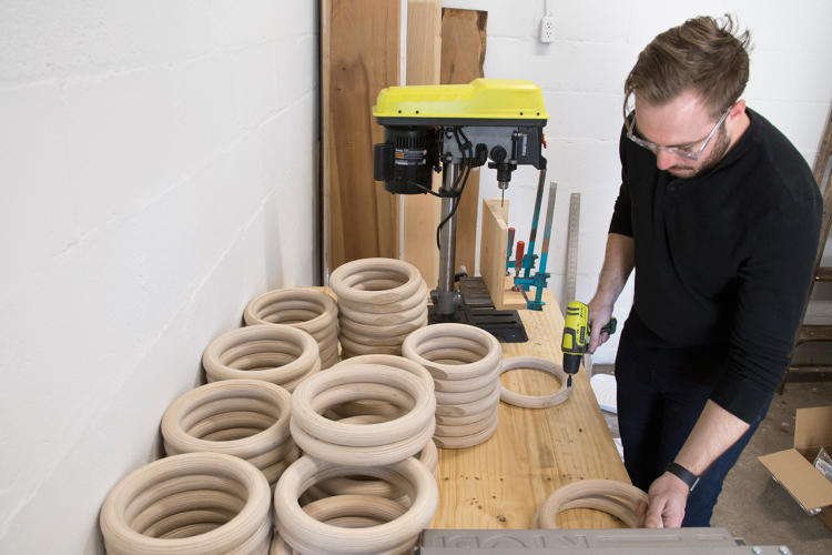 <p>Yield's operations manager Ryan Tempro creating their wooden planter rings for hanging plants on the wall.</p>
