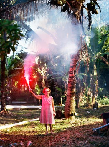 <p>Seamstress Vo' Zeze in her garden in the community of Colonia J. Moreira. The TransOlympic Highway is now a stone-throw away from her home.</p>