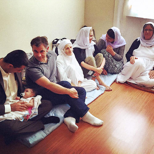 <p>Elizabeth Schaeffer-Brown and Kerry Propper visiting with Yazda founder Murad Ismael's relatives in Dohuk. After ISIS attacked Sinjar, 13 members of his family moved into the apartment. This picture shows four generations of his family.</p>