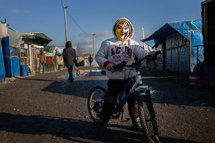 <p>A kid on his bike, wearing a mask that he painted himself in a painting workshop organized by volunteers at the camp.</p>